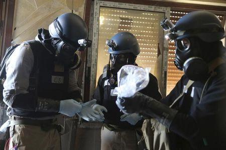 FILE PHOTO: A U.N. chemical weapons expert, wearing a gas mask, holds a plastic bag containing samples from one of the sites of an alleged chemical weapons attack in the Ain Tarma neighbourhood of Damascus August 29, 2013.  REUTERS/Mohamed Abdullah