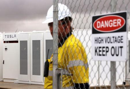A worker stands next to the main gate of the compound for the Hornsdale Power Reserve, featuring the world's largest lithium ion battery made by Tesla, during the official launch near the South Australian town of Jamestown, in Australia, December 1, 2017. REUTERS/David Gray