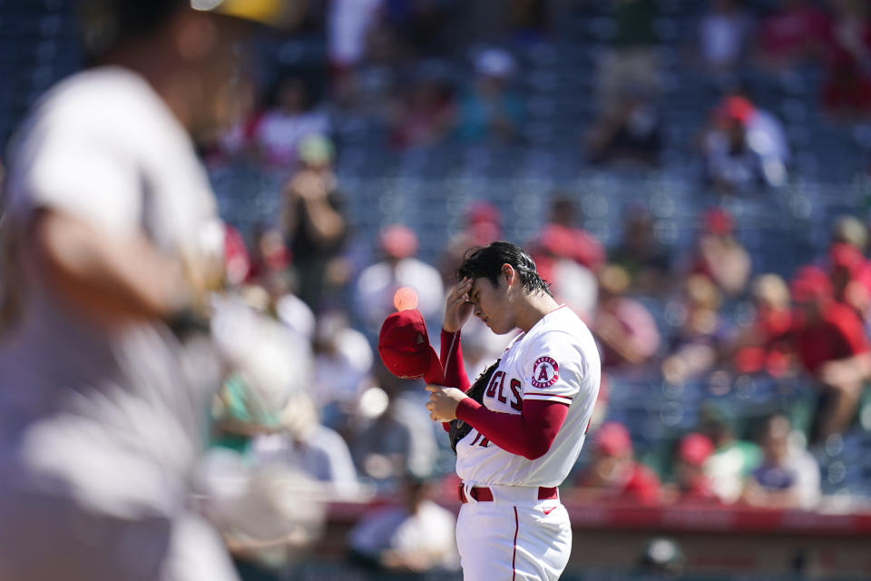Los Angeles Angels starting pitcher Shohei Ohtani, right, of Japan, adjusts his cap after giving up a home run to Oakland Athletics' Yan Gomes, foreground, during the third inning of a baseball game Sunday, Sept. 19, 2021, in Anaheim, Calif. (AP Photo/Jae C. Hong)