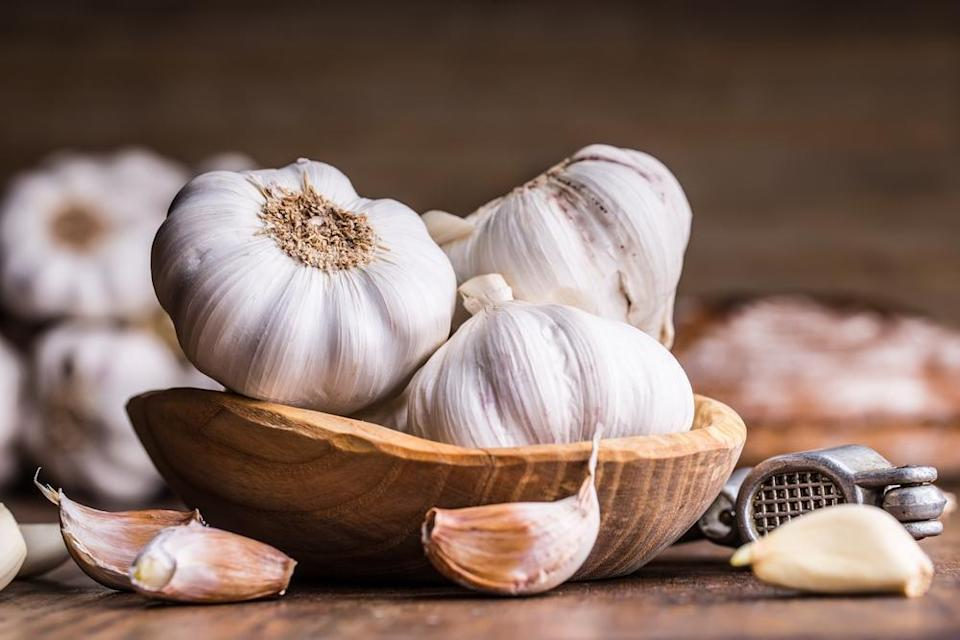 """<p>You should always buy whole, unpeeled bulbs of garlic — not only do they taste fresher but they also last longer. (If you buy pre-prepped garlic because you hate taking the skins off, <a href=""""https://www.thedailymeal.com/cook/garlic-peeling-hack?referrer=yahoo&category=beauty_food&include_utm=1&utm_medium=referral&utm_source=yahoo&utm_campaign=feed"""" rel=""""nofollow noopener"""" target=""""_blank"""" data-ylk=""""slk:try this genius hack that chefs use to peel them"""" class=""""link rapid-noclick-resp"""">try this genius hack that chefs use to peel them</a>.) To tell if your garlic has gone bad, look for dark spots, signs of rot, or patches of green growth. You can also squeeze the garlic and if it feels too soft, it should be thrown away.</p>"""