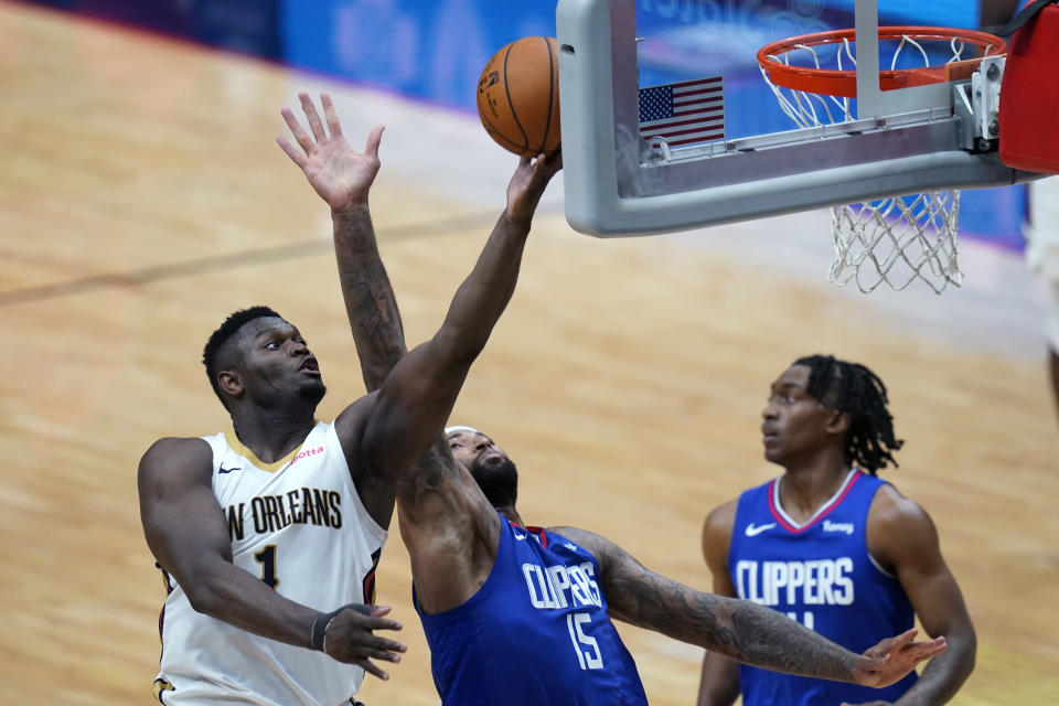 New Orleans Pelicans forward Zion Williamson (1) goes to the basket against LA Clippers center DeMarcus Cousins (15) in the second half of an NBA basketball game in New Orleans, Monday, April 26, 2021. The Pelicans won 120-103. (AP Photo/Gerald Herbert)