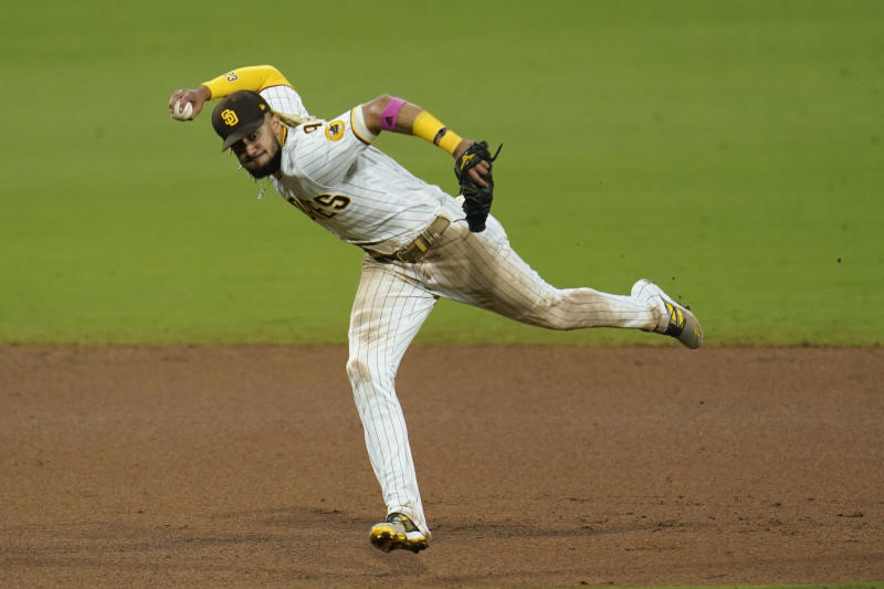 San Diego Padres shortstop Fernando Tatis Jr. throws to first too late as Los Angeles Angels' Luis Rengifo arrives safely for a single during the eighth inning of a baseball game Tuesday, Sept. 22, 2020, in San Diego. (AP Photo/Gregory Bull)