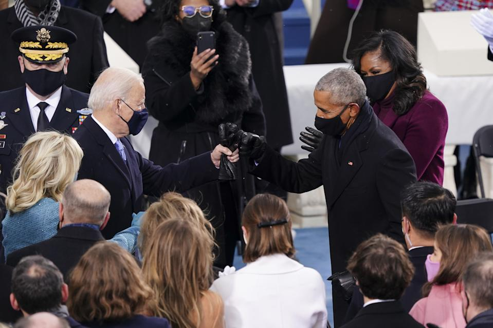 U.S. President-elect Joe Biden, left, greets former U.S. President Barack Obama, right, with a fist bump during the 59th presidential inauguration. (Kevin Dietsch/UPI/Bloomberg via Getty Images)
