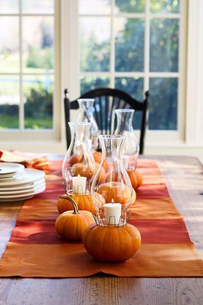 """<p>Looking for an unexpected candle arrangement? Consider using mini pumpkins as votive holders. Just remove the pumpkin's stem and place a candle right on top. Cover it with a glass hurricane and insert floral U-pins to keep them in place. <br></p><p><a class=""""link rapid-noclick-resp"""" href=""""https://go.redirectingat.com?id=74968X1596630&url=https%3A%2F%2Fwww.michaels.com%2F12-white-glass-votive-candles-ashland-basic-elements%2F10136302.html&sref=https%3A%2F%2Fwww.goodhousekeeping.com%2Fholidays%2Fhalloween-ideas%2Fg33437890%2Fhalloween-table-decorations-centerpieces%2F"""" rel=""""nofollow noopener"""" target=""""_blank"""" data-ylk=""""slk:SHOP VOTIVES"""">SHOP VOTIVES</a></p>"""