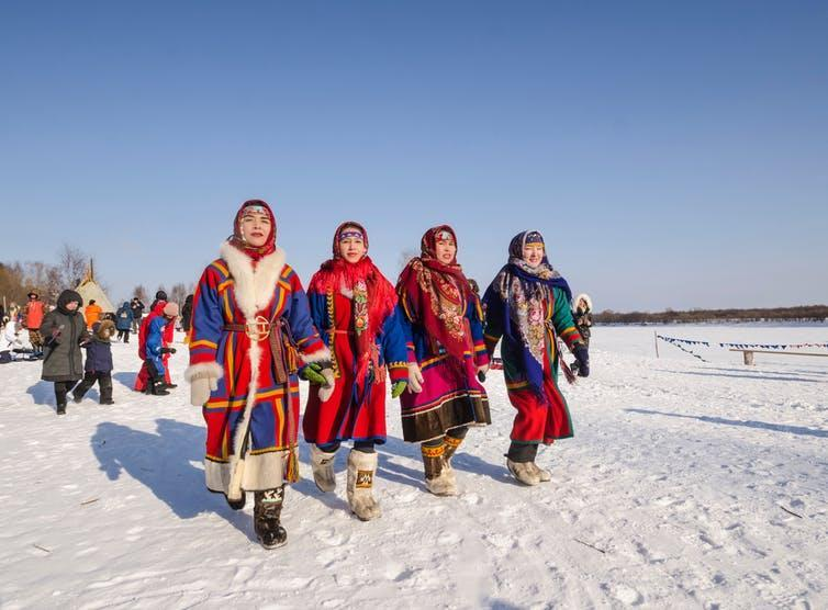 Four young women wearing brightly coloured traditional dress walk over snow.