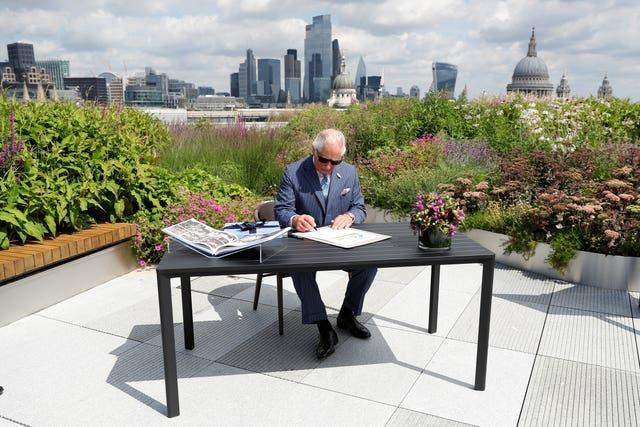 The Prince of Wales signs a document commemorating his visit to Goldman Sachs in central London