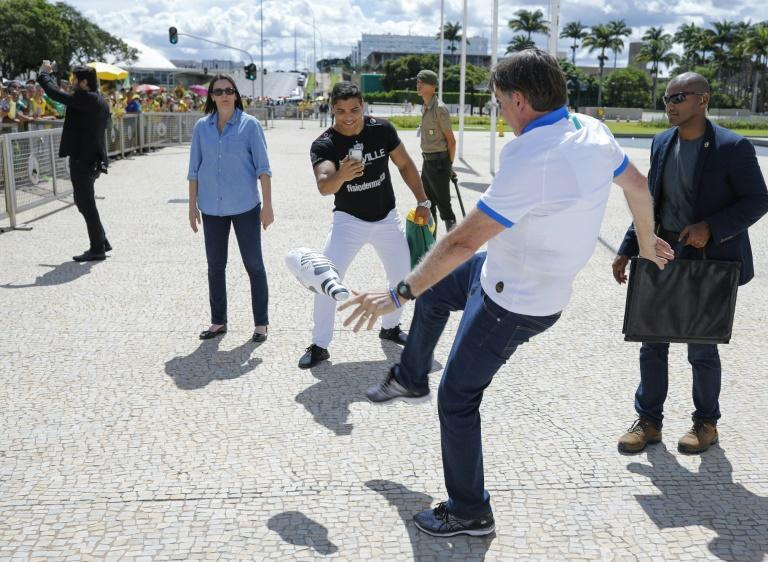 Brazilian President Jair Bolsonaro kicks a dummy of Lula da Silva after a protest against the National Congress and the Federal Supreme Court, in Brasilia, on March 15, 2020