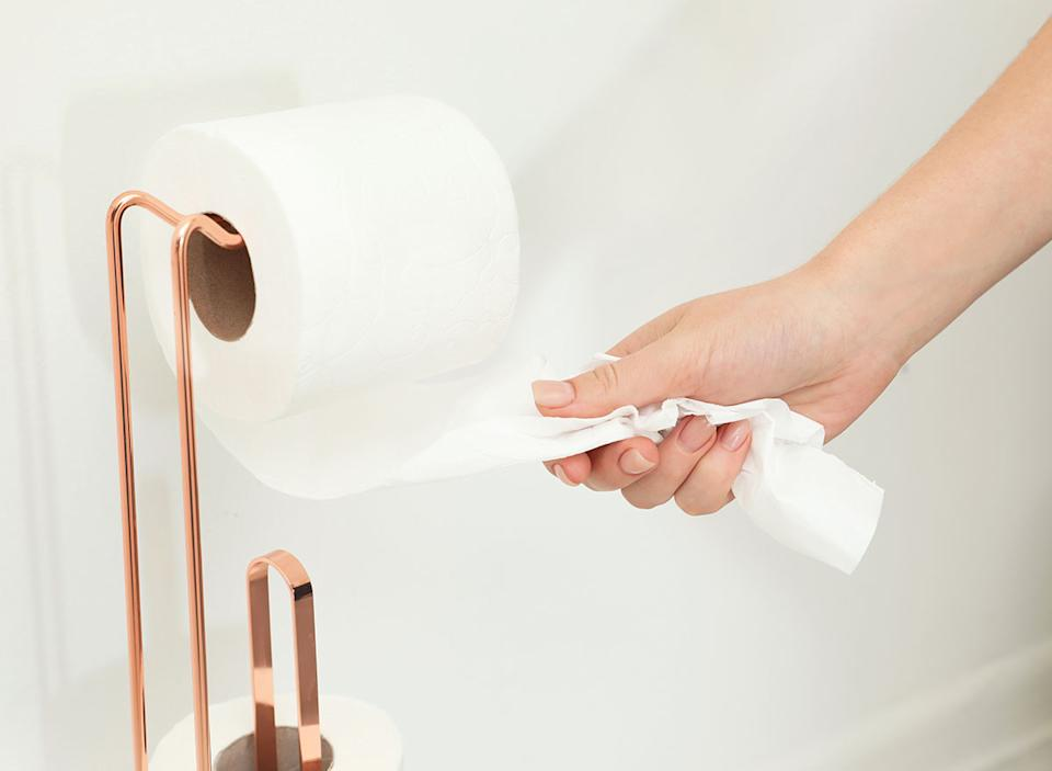 Woman grabbing toilet paper from the roll.