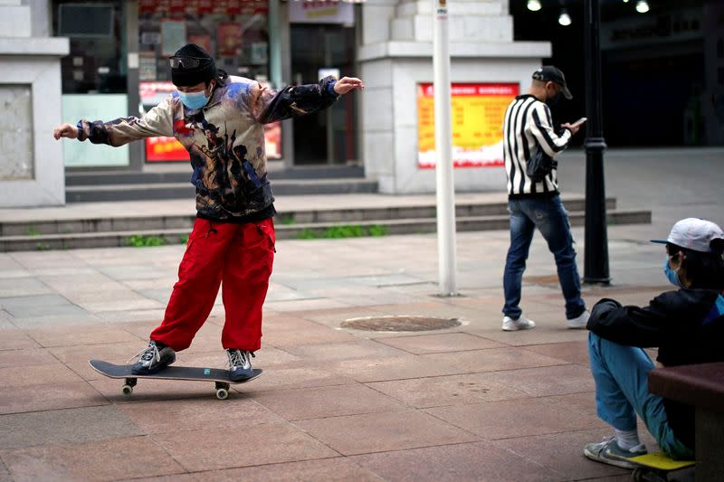 Man wearing a face mask skateboards on a street in Wuhan