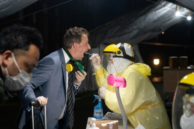 Worker in protective suit collects a throat swab specimen from a passenger coming from Australia for the test of the novel coronavirus that causes COVID-19 in Shanghai