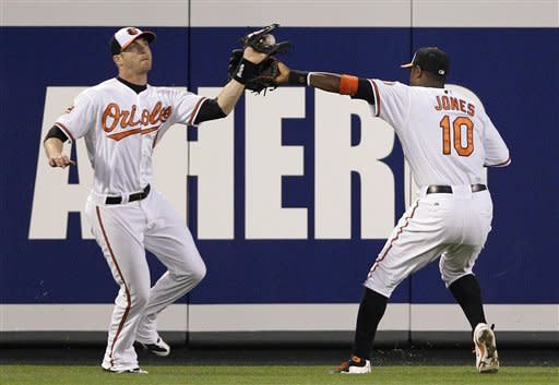 Baltimore Orioles center fielder Adam Jones, right, tries to avoid left fielder Nolan Reimold as Reimold catches a fly ball hit by Toronto Blue Jays' Jose Bautista in the fourth inning of a baseball game in Baltimore, Thursday, April 26, 2012. (AP Photo/Patrick Semansky)
