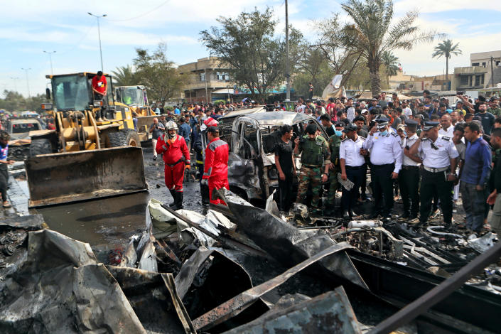 People and security forces inspect the scene of an explosion at a crowded outdoor used furniture market in Sadr City area, Iraq, Thursday, April 15, 2021. The powerful explosion rocked the market in east Baghdad on Thursday, killing at least one person and injuring many others, according to Iraq's military. The cause of the blast was not immediately known. (AP Photo/Khalid Mohammed)