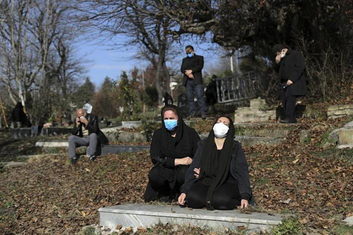 FILE - In this Dec. 17, 2020, file photo, mourners attend the funeral of a woman who died from COVID-19 at a cemetery in the outskirts of the city of Ghaemshahr, in northern Iran. The global death toll from COVID-19 has topped 2 million. (AP Photo/Ebrahim Noroozi, File)