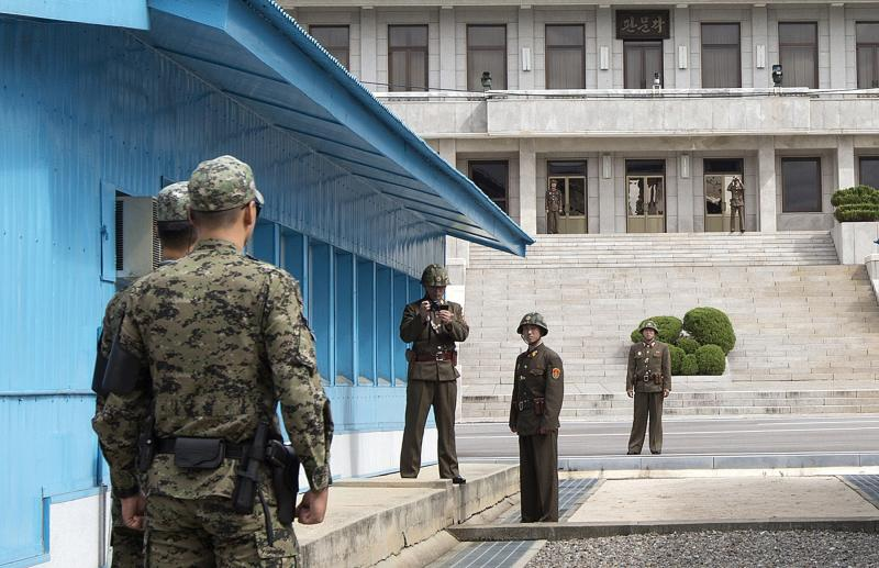North Korean soldiers stand on the North Korean side, with one using a camera, as South Korean soldiers face them on the border of the DMZ, in Panmunjom