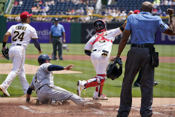 Umpire C.B. Bucknor, right, calls Milwaukee Brewers' Manny Pina (9) out when Pina was attempting to score on a bunt by Freddy Peralta as Pittsburgh Pirates catcher Michael Perez, second from right, throws to first to complete a double play on Peralta and end the top of the second inning of a baseball game in Pittsburgh, Sunday, July 4, 2021. (AP Photo/Gene J. Puskar)