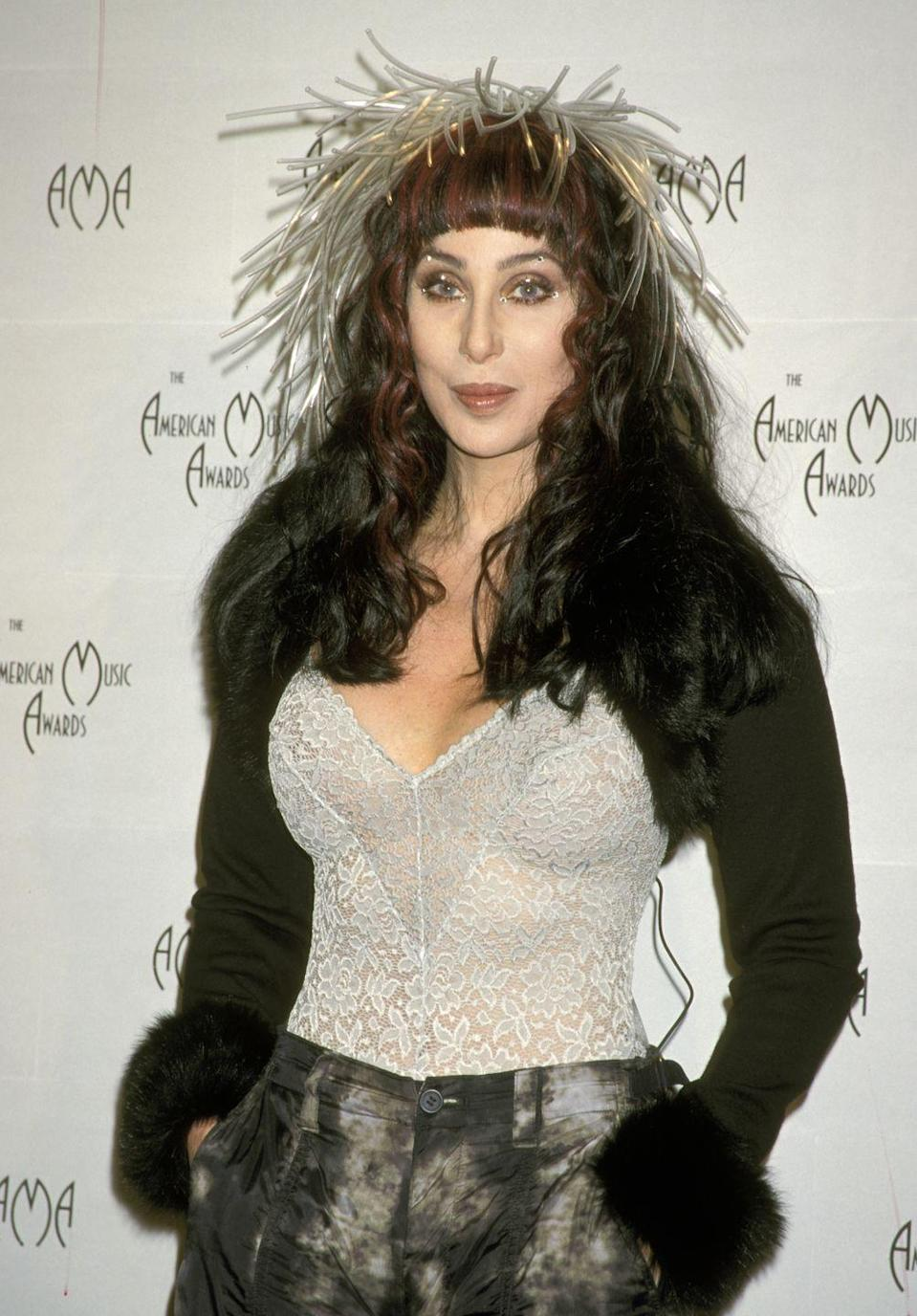<p>In a sheer lace corset, fur-trimmed cardigan, and Medusa-inspired headpiece at the 1999 American Music Awards. </p>