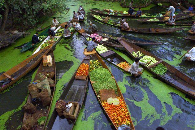 Kashmiri vegetable sellers gather at a floating market on Dal Lake in Srinagar, the summer capital of Jammu and Kashmir state in August 11, 2002.