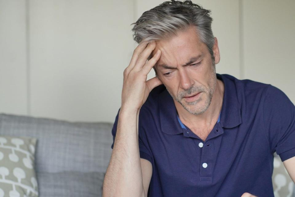 Mature man with bad headache at home