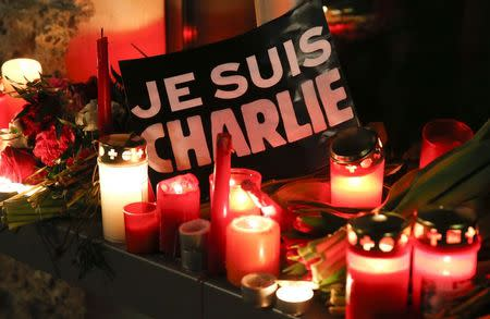 """Candles and a placard which reads """"I am Charlie"""" are pictured as tributes to victims at the French embassy at Pariser Platz in Berlin January 7, 2015, following a shooting by gunmen at the offices of weekly satirical magazine Charlie Hebdo in Paris. REUTERS/Fabrizio Bensch"""