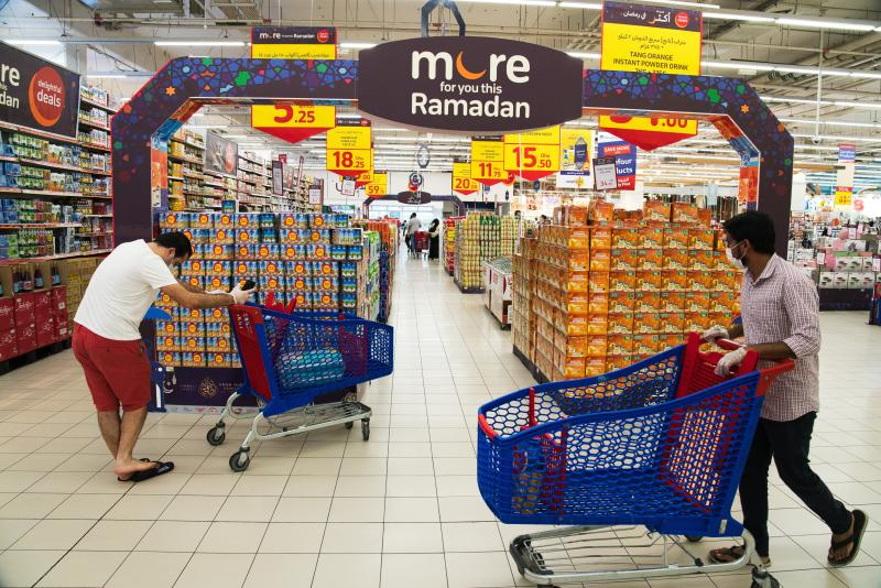 In this Sunday, April 19, 2020 photo, shoppers wearing face masks and gloves amid the coronavirus pandemic pass by a Ramadan display at a Carrefour supermarket in Dubai, United Arab Emirates. As Ramadan begins with the new moon later this week, Muslims all around the world are trying to work out how to maintain the many cherished rituals of Islam's holiest month as much as possible -- without further spreading the outbreak. Many of those traditions are now impossible as authorities try to clamp down against the pandemic. (AP Photo/Jon Gambrell)