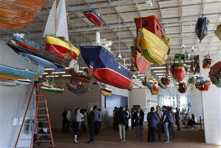 """Media members stand near a work titled """"For Those in Peril on the Sea"""" by artist Hew Locke during a tour of the PAMM in Miami, Florida"""