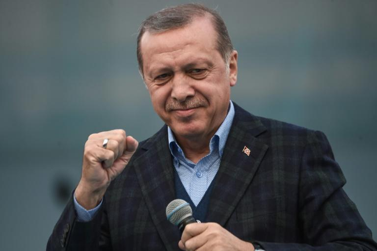 "Turkish President Recep Tayyip Erdogan gestures as he delivers a speech on April 8, 2017 during a campaign rally for the ""yes"" vote in a constitutional referendum in Istanbul"