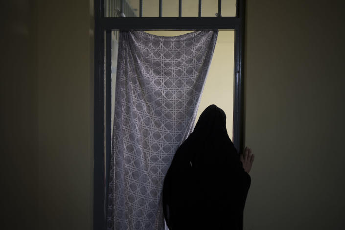 An Afghan woman walks out of a cell inside the women's section of the Pul-e-Charkhi prison in Kabul, Afghanistan, Thursday, Sept. 23, 2021. When the Taliban took control of a northern Afghan city of Pul-e-Kumri the operator of the only women's shelter ran away, abandoning 20 women in it. When the Taliban arrived at the shelter the women were given two choices: Return to their abusive families, or go with the Taliban, With nowhere to put the women, the Taliban took them to the abandoned women's section of Afghanistan's notorious Pul-e-Charkhi prison. (AP Photo/Felipe Dana)