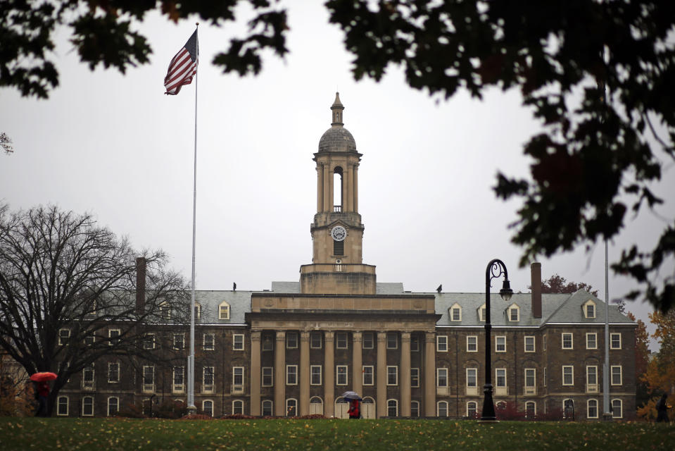 """In this Oct. 28, 2015 file photo, a Penn State student walks in the rain past Old Main on the Penn State main campus in State College, Pa. Under a new proposal, a metro area would have to have at least 100,000 people to count as an MSA, double the 50,000-person threshold that has been in place for the past 70 years. Cities formerly designated as metros with core populations between 50,000 and 100,000 people would be changed to """"micropolitan"""" statistical areas instead. (AP Photo/Gene J. Puskar, File)"""