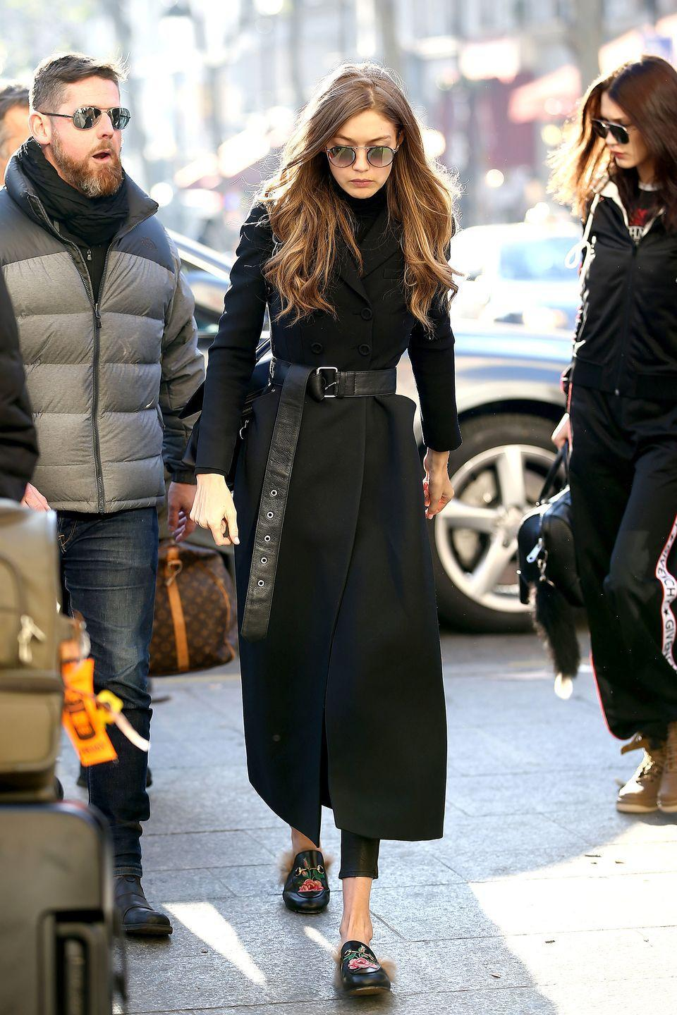 <p>In a belted long black trench coat, turtleneck, leather leggings, furry Gucci loafers and rounded sunglasses while leaving Paris. </p>