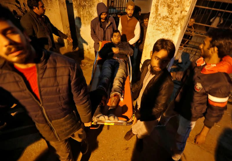 A injured man is shifted to a hospital after he was wounded during a protest against a new citizenship law, in New Delhi