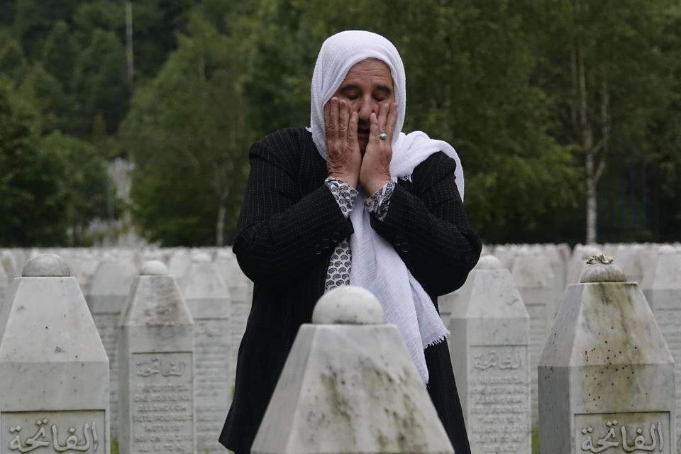 Munira Subasic who lost her son and the husband in Srebrenica massacre prays at the memorial cemetery in Potocari near Srebrenica, Bosnia, Friday, May 28, 2021. U.N. judges on Tuesday, June 8 deliver their final ruling on the conviction of former Bosnian Serb army chief Radko Mladic on charges of genocide, war crimes and crimes against humanity during Bosnia's 1992-95 ethnic carnage. Nearly three decades after the end of Europe's worst conflict since World War II that killed more than 100,000 people, a U.N. court is set to close the case of the Bosnian War's most notorious figure. (AP Photo/Eldar Emric)