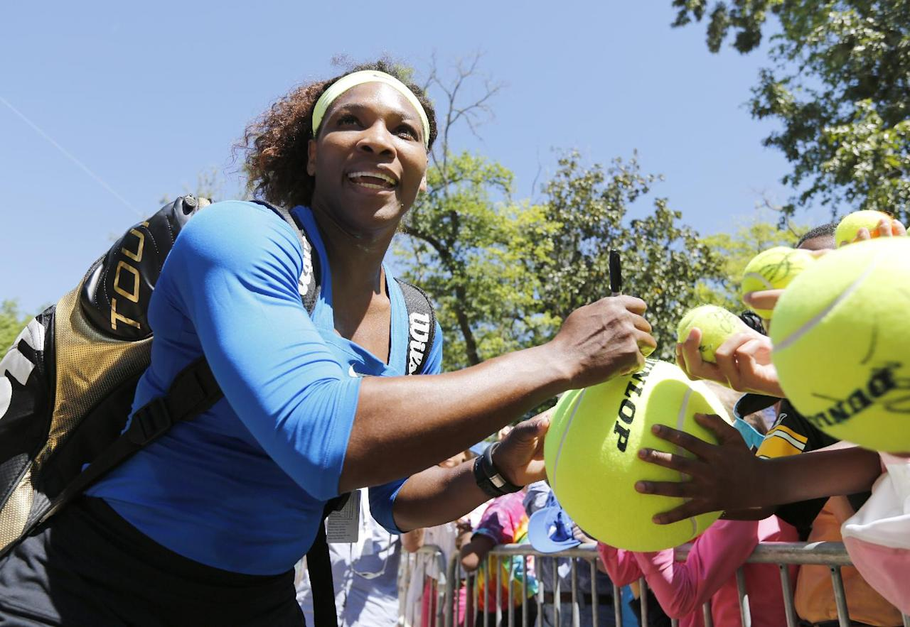 Serena Williams signs autographs for fans after her semifinal match against Samantha Stosur, of Australia, at the Family Circle Cup tennis tournament in Charleston, S.C., Saturday, April 7, 2012. Williams advanced to the finals by winning 6-1, 6-1. (AP Photo/Mic Smith)