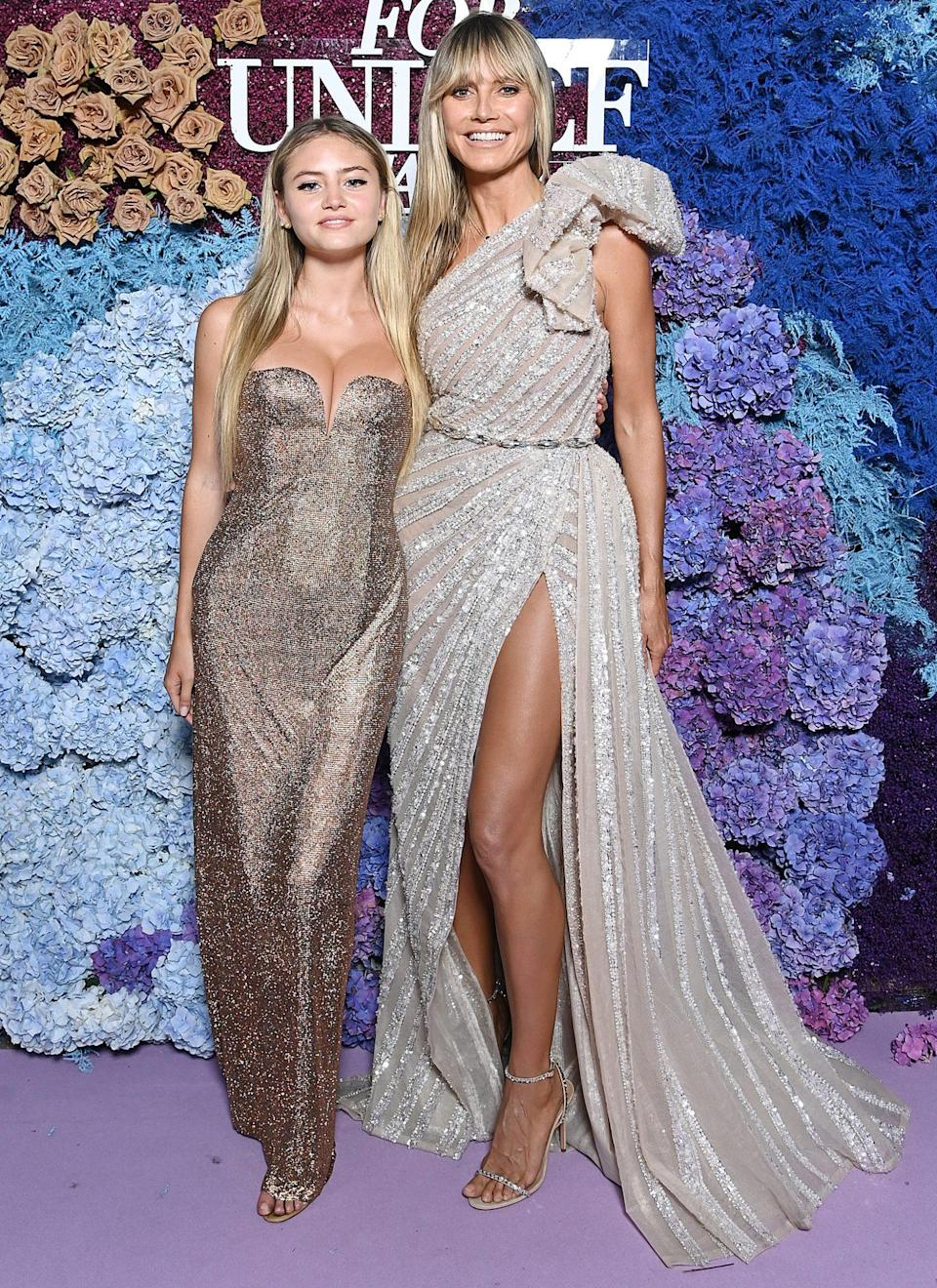 """<p><a href=""""https://people.com/style/heidi-klum-walks-unicef-red-carpet-with-daughter-leni/"""" rel=""""nofollow noopener"""" target=""""_blank"""" data-ylk=""""slk:coordinate in glittery gowns"""" class=""""link rapid-noclick-resp"""">coordinate in glittery gowns</a>. Leni wears a high-shine Versace gown with sweetheart-style neckline and an open back, while Heidi sparkles in a one-shoulder belted Elie Saab gown with a side slit and train. </p>"""