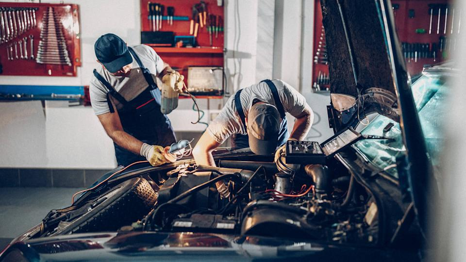 Two man working on repair of old timer.