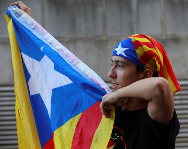 <p>A protestor holds up an Estelada (Catalan separatist flag) outside a Unipost office which was raided in search of material for the proposed October 1 referendum, in Terrassa, Spain, Sept. 19, 2017. (Photo: Albert Gea/Reuters) </p>