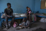 Tigrayan 11-year-old refugee Daniel Gebremariam holds his 4-month-old sister, Turfu, as his 5-year-old brother, Micheale, eats with their 19-year-old uncle, Goytom Tsegay, left, inside the family's shelter in Hamdayet, eastern Sudan, near the border with Ethiopia, on March 21, 2021. (AP Photo/Nariman El-Mofty)
