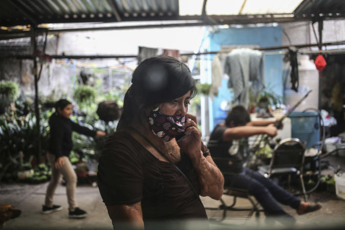 Elisa Xolalpa, who survived an acid attack while tied to a post by her ex-partner 20 years ago when she was 18, talks on a cell phone as her children play at her parents' house in Mexico City, Sunday, July 4, 2021. Xolapa said we can't allow the violence to be normalized and that's a message she wants to teach her daughters. (AP Photo/Ginnette Riquelme)