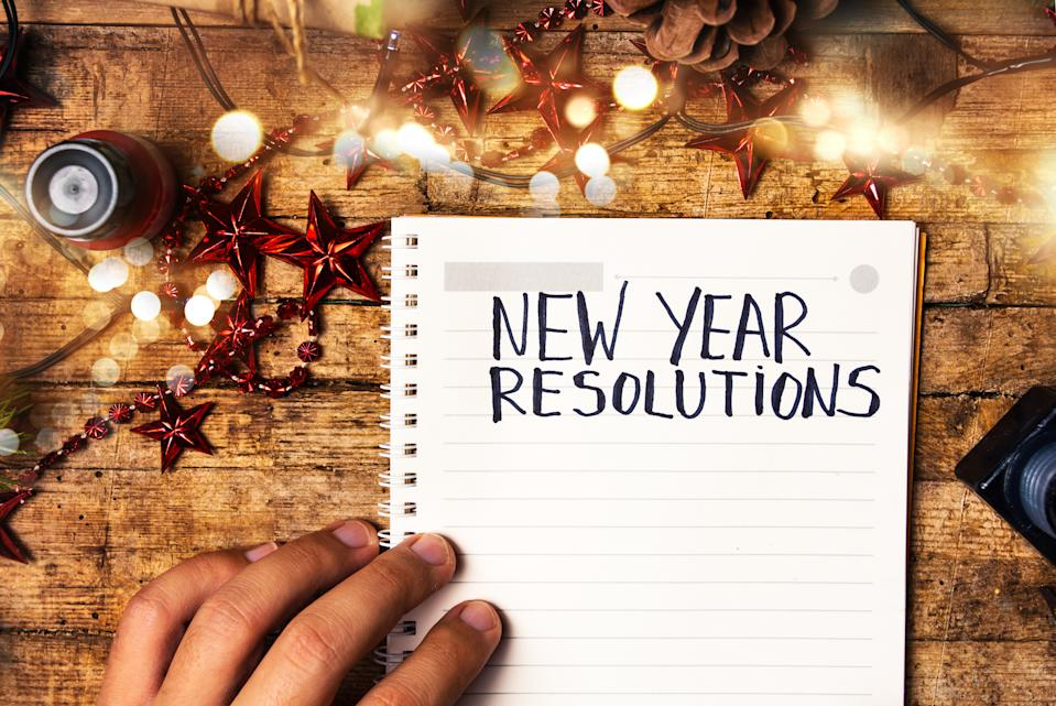 Person writing new year resolutions first person view