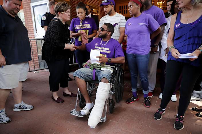 Marcus Martin (center), who was injured in the same car attack that killed Heyer, leaves the memorial service.