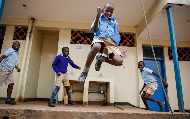 Schoolchildren joke around and play at a school in Kibera, one of the capital city's poorest areas. Kenya partially re-opened schools on Monday to allow those students due for examinations which had been postponed to prepare, following a total closure of all educational institutions enacted since March - AP Photo/Brian Inganga