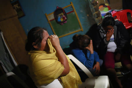 Edith Mora Mora Venancio, sister of Alexander Mora Venancio mourns next to others women at their house in El Pericon, in the southern Mexican state of Guerrero, December 6, 2014. REUTERS/Jorge Dan Lopez