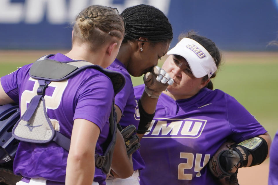 James Madison's Odicci Alexander, center, stands with teammates Lauren Bernett (22) and Lynsey Meeks (24) as she is taken out as pitcher in the fifth inning of an NCAA Women's College World Series softball game against Oklahoma, Monday, June 7, 2021, in Oklahoma City. (AP Photo/Sue Ogrocki)