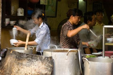 Dishing up pho at a restaurant in Hanoi - Credit: GETTY