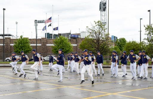Minnesota NCAA college baseball players warm up in wet weather in a parking lot adjacent to TD Ameritrade Park in Omaha, Neb., Tuesday, May 22, 2018, ahead of the Big Ten tournament. Minnesota is the top seed, Purdue is red hot, and defending champion Iowa is looking to get to the title game for the third straight year. The Big Ten Tournament looks to be wide open as it returns to TD Ameritrade Park for the third time since 2014. (AP Photo/Nati Harnik)