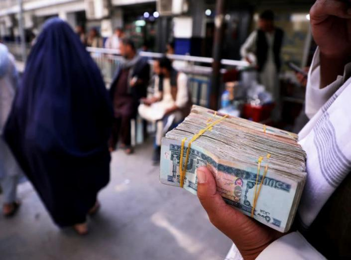 FILE PHOTO: Person holds a bundle of Afghan afghani banknotes at a money exchange market in Kabul