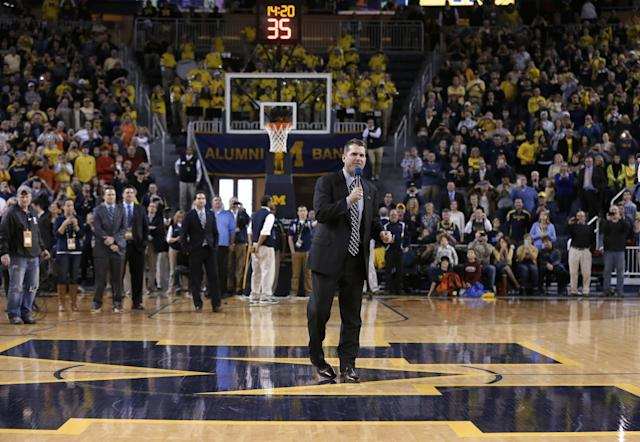 Michigan football coach Jim Harbaugh greets fans during halftime of an NCAA college basketball game between Michigan and Illinois in Ann Arbor, Mich., Tuesday, Dec. 30, 2014. (AP Photo/Carlos Osorio)