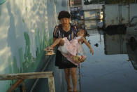 A woman carries a child in her arms as she walks on a curb above floodwaters in Xinxiang in central China's Henan Province, Monday, July 26, 2021. Record rain in Xinxiang last week left the produce and seafood market soaked in water. Dozens of people died in the floods that immersed large swaths of central China's Henan province in water. (AP Photo/Dake Kang)
