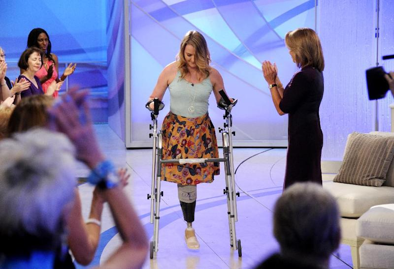 """This image released by Disney-ABC Domestic Television shows host Katie Couric, right, applauding as Aimee Copeland, 24, of Snellville, Ga., who survived a rare fleshing-eating disease, as she arrives for an exclusive interview on the new daytime talk show """"Katie,"""" Tuesday, Sept. 11, 2012, in New York. Copeland walked to the stage using a new walker. Copeland was joined in New York by her parents and sister. After Couric interviewed the family, she announced that an Atlanta-area Chevrolet dealer was in the studio to give Copeland a new minivan that will be retrofitted so she can drive it. Copeland got the infection in May after falling from a zip line and gashing her leg. Doctors had to amputate both hands, her left leg and right foot. She returned home to suburban Atlanta last week after three months in the hospital and a rehabilitation clinic. (AP Photo/Disney-ABC Domestic Television, Ida Mae Astute)"""