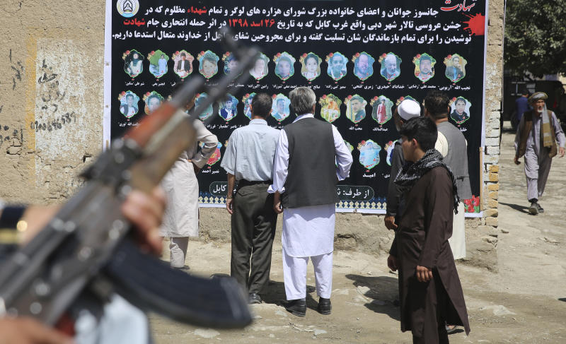 Afghans look at a banner displaying photographs of victims of the Dubai City wedding hall bombing during a memorial service, in Kabul, Afghanistan, Tuesday, Aug. 20, 2019. Hundreds of people have gathered in mosques in Afghanistan's capital for memorials for scores of people killed in a horrific suicide bombing at a Kabul wedding over the weekend.(AP Photo/Rafiq Maqbool)