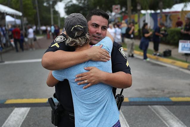 <p>University Of Central Florida Police officer Pablo Vargas receives a hug from Christine Gigicos as they attend the one-year anniversary memorial service for victims of the mass shooting at the Pulse gay nightclub on June 12, 2017 in Orlando, Florida. (Joe Raedle/Getty Images) </p>